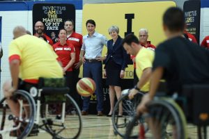 Prime Ministers Justin Trudeau and Theresa May watch from the sidelines during a Canada/UK demo match.